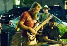 man in red shirt playing guitar